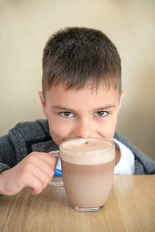 O chocolate caucasiano do menino no café, sorriso e olha a câmera.