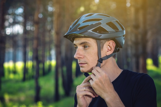 O ciclista do homem está vestindo um capacete cinzento dos esportes em sua cabeça no fundo da natureza verde.