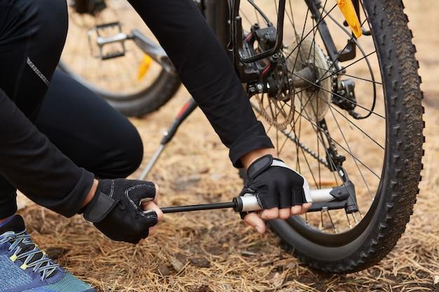 O ciclista em esportes pretos usa segurando a bomba com as duas mãos, usando-a para bombear pneus, tendo problemas com movimentos adicionais
