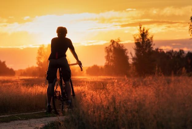 O ciclista em uma bicicleta de cascalho fica em um campo em um fundo bonito por do sol.