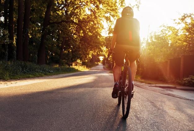 O ciclista está treinando em uma bicicleta ao ar livre em uma noite de verão ao pôr do sol.