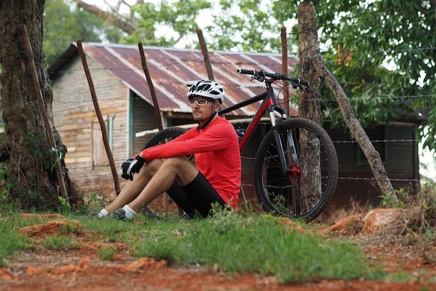 O ciclista masculino senta-se na grama perto de uma casa abandonada na natureza.