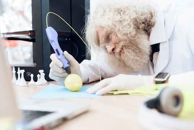 O cientista com barba cinzenta pinta a maçã verde com o punho 3d.