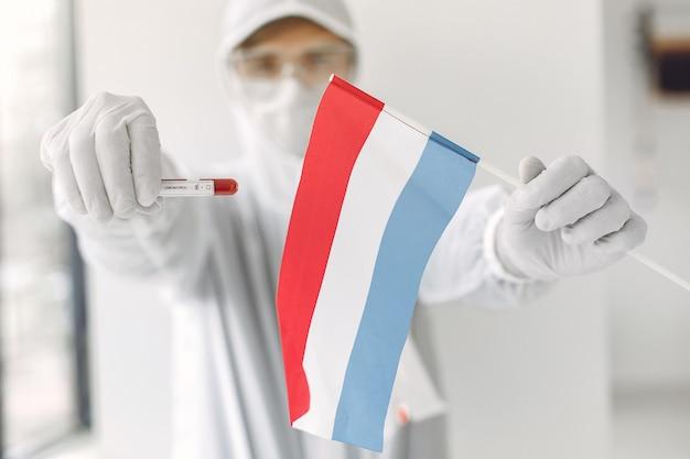 O cientista de macacão com uma amostra de coronavírus e a bandeira da holanda
