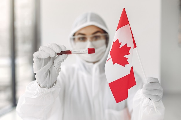 O cientista de macacão com uma amostra de coronavírus e bandeira do canadá