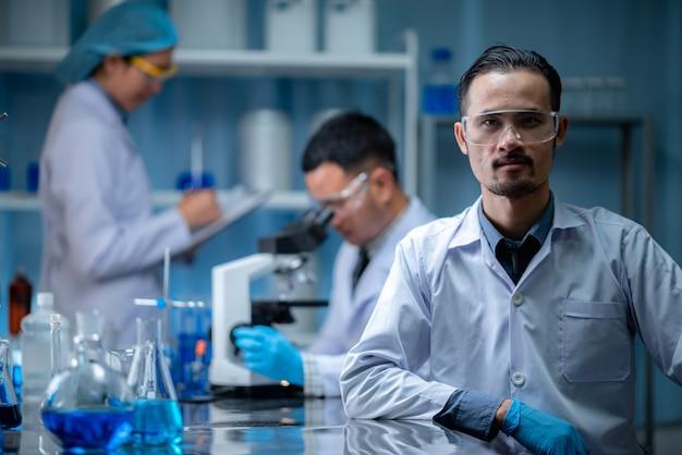O cientista especialista em trabalho em equipe ou pesquisador testa e desenvolve o experimento da vacina química com drogas através do microscópio no moderno laboratório biológico