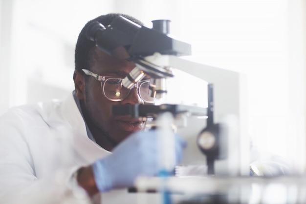O cientista trabalha com um microscópio em um laboratório conduzindo experimentos e fórmulas.
