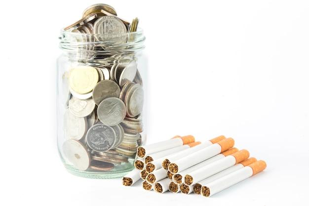 O cigarro e a moeda com saúde e salvar o conceito da ideia isolado no fundo branco.