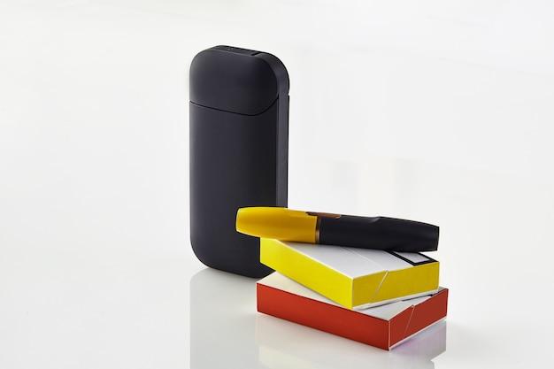 O cigarro eletrônico preto de nova geração está na bateria das caixas de fósforos vermelha e amarela ...