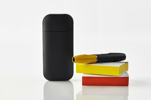 O cigarro eletrônico preto de nova geração está na bateria de caixas de fósforos vermelha e amarela
