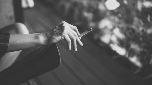 O cigarro na mão da mulher.