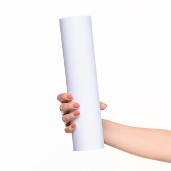 O cilindro branco dos adereços nas mãos femininas sobre fundo branco com sombra direita
