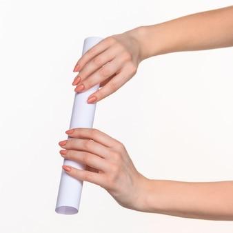 O cilindro nas mãos femininas na parede branca