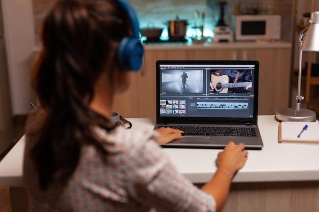O cineasta editando um filme usando um software moderno para o criador de conteúdo de pós-produção em trabalho doméstico ...