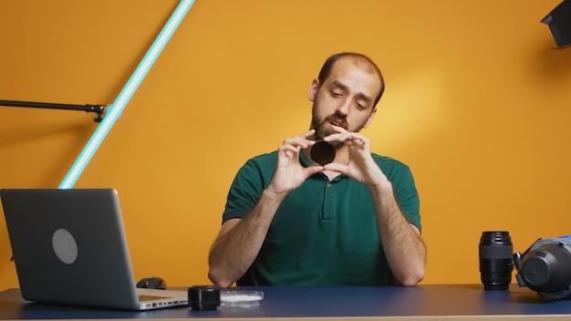 O cinegrafista examinando o filtro nd enquanto grava a revisão de seu vlog. revisão do filtro nd variável, equipamento da câmera e vídeo do equipamento. ceator influenciador estrela de mídia social distribuindo conteúdo online