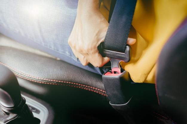 O cinto de segurança do uso da jovem mulher antes de começa o carro. conceito de segurança.