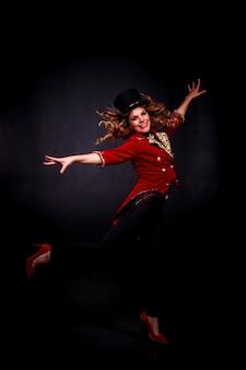 O circo ilusionista mágico feminino em roupas teatrais salta e sorri, sobre fundo preto. atriz mulher com fantasia de palco e cartola na cabeça. conceito de desempenho. copie o espaço