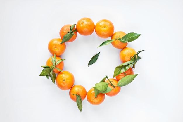 O círculo de tangerinas ou dos mandarino frescos alaranjados com folhas verdes encontra-se em um fundo branco. vista do topo.