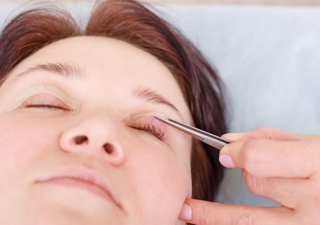 O cirurgião aplica um curativo nas pálpebras da paciente após