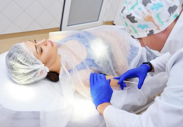 O cirurgião faz uma injeção de anestesia no paciente da mulher antes de remover a toupeira.