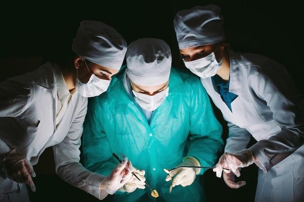 O cirurgião faz uma operação em um quarto escuro.