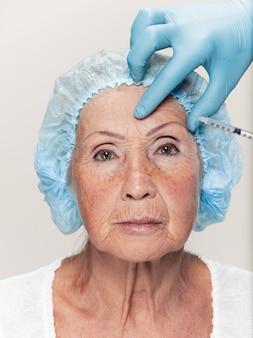 O cirurgião fazendo uma verificação de pele em uma mulher de meia-idade antes da cirurgia plástica. modelo feminino sênior. cirurgia plástica, levantamento, conceito de envelhecimento