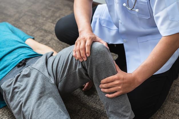 O cirurgião ortopédico profissional está examinando o joelho de um paciente na clínica.