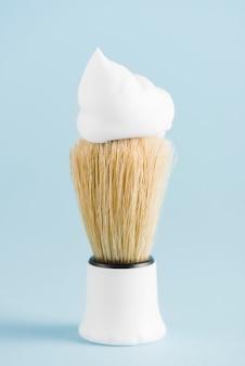 O clássico pincel de barba com espuma contra o pano de fundo azul