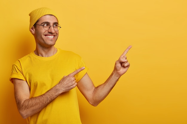O cliente de um homem sorridente e de aparência amigável anuncia a venda no espaço de cópia certo, aponta o dedo indicador, recomenda ir nesta direção