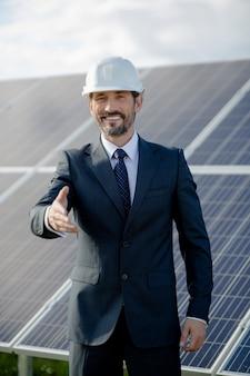 O cliente do negócio na estação solar feliz e apronta-se ao aperto de mão.