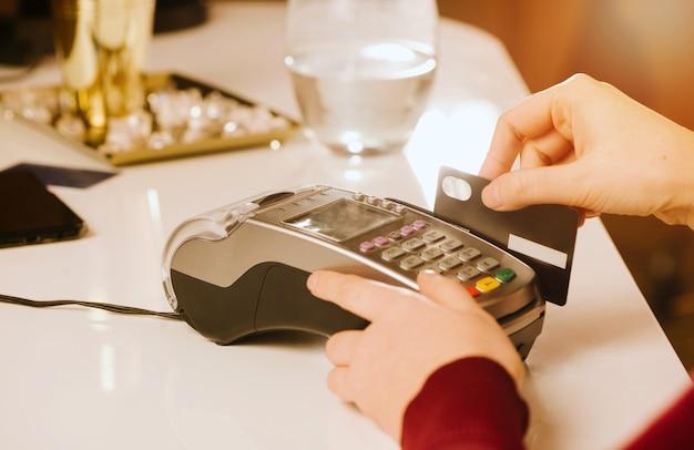 O cliente faz o pagamento usando cartão de crédito, visualização do dispositivo de mãos, método sem dinheiro para pagar contas em conceito de espaços comerciais