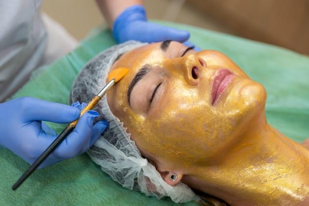 O cliente faz um procedimento para o tratamento de uma máscara de close-up de ouro