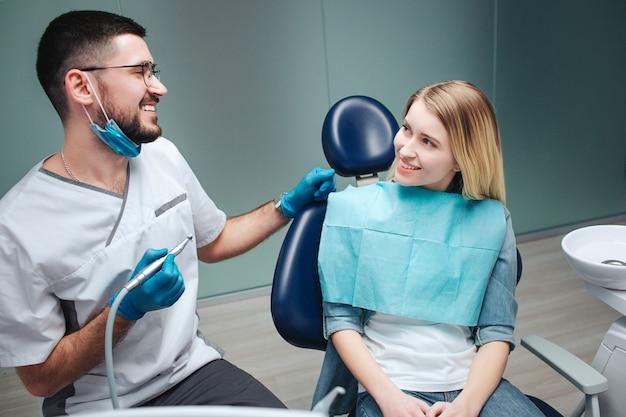 O cliente fêmea novo feliz senta-se na cadeira na odontologia. ela olha para o dentista e sorri. homem novo na máscara e rob branco que guarda a máquina para o tratamento dos dentes.