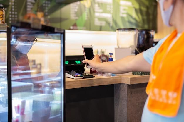 O cliente masculino novo de nomarl que paga a conta pelo telefone celular com equipe behid a divisória plástica no café.