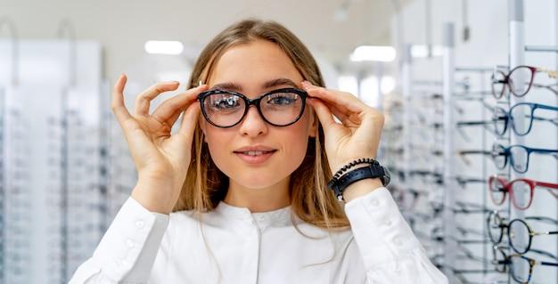 O cliente ou oculista fêmea feliz está de pé com um conjunto de óculos no fundo na loja de óptica.