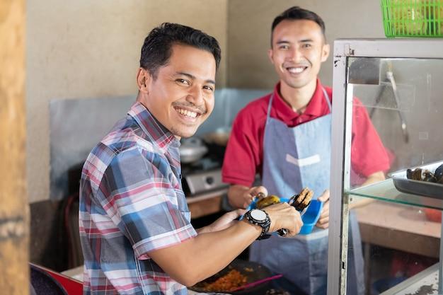 O cliente sorri escolhendo acompanhamentos quando o vendedor é servido segurando uma bandeja com um fundo de barraca de comida