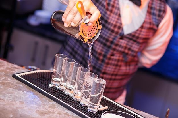 O close da mão do barman no trabalho, ele preparando coquetéis. conceito sobre serviço e bebidas.