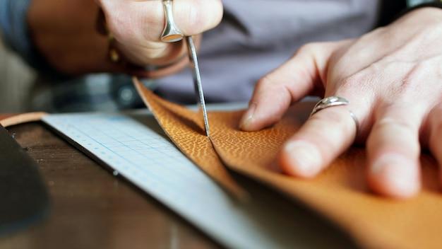 O close das mãos dos homens corta um pedaço de couro genuíno para fazer uma carteira.