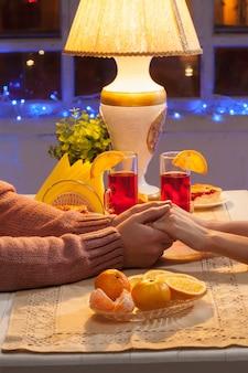 O close de mãos do feliz casal jovem com xícaras de chá e frutas