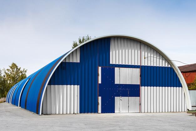 O close-up da bandeira nacional da finlândia pintou na parede do metal de um grande armazém o território fechado contra o céu azul. o conceito de armazenamento de mercadorias, entrada em uma área fechada, logística