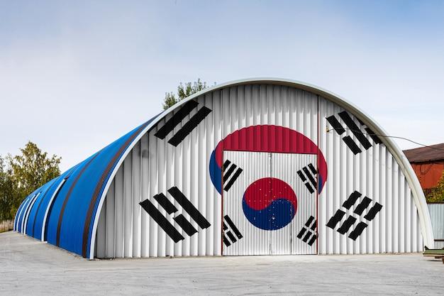 O close-up da bandeira nacional de coreia do sul pintou na parede do metal de um grande armazém o território fechado contra o céu azul.