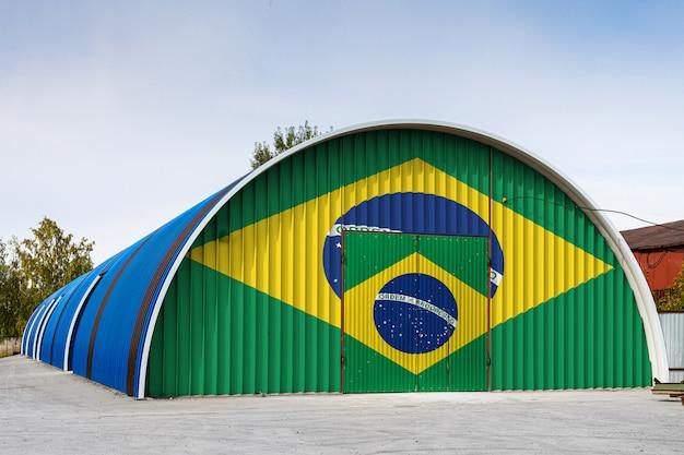 O close-up da bandeira nacional do brasil pintou na parede do metal de um grande armazém o território fechado contra o céu azul. o conceito de armazenamento de mercadorias, entrada em uma área fechada, logística