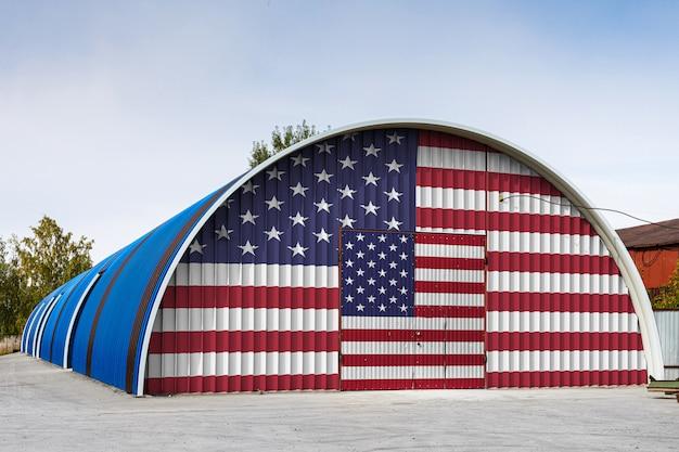 O close-up da bandeira nacional dos eua pintou na parede do metal de um grande armazém o território fechado contra o céu azul.