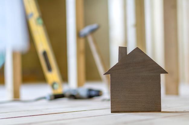 O close-up da casa modelo marrom pequena simples na construção borrada utiliza ferramentas o fundo. construção, construção e investimentos em imóveis, propriedade e propriedade do conceito de casa de sonho.