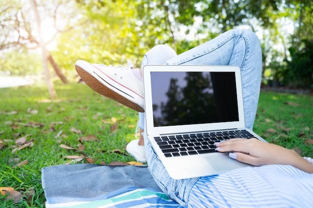 O close up da jovem mulher que usa o portátil com relaxa no jardim.