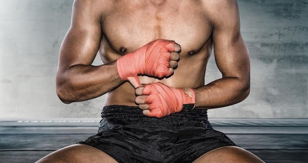 O close-up da mão boxer puxa envoltórios de pulso antes do treino.