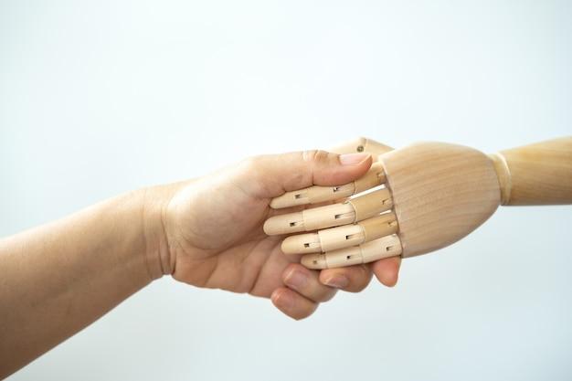 O close up da mão da mulher faz um aperto de mão com a mão de madeira no fundo branco.