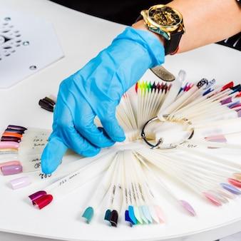O close up da mão das mestras do salão de manicure mostra opções de esmaltes coloridos