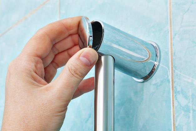 O close up da mão humana fecha o chuveiro do suporte da montagem da parede do suporte de fixação da tampa no banheiro.