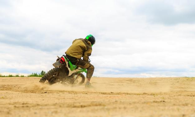 O close-up da montanha motocross compete na trilha de terra no tempo do dia.